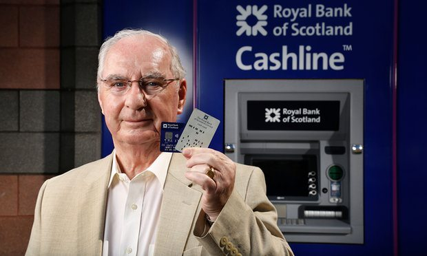 ATM inventor James Goodfellow with one of the early 'coded bank tokens' and a modern day card. Photograph: Murdo Macleod for the Guardian